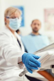 Primo piano del medico stomatologo che prepara gli strumenti dentali per la chirurgia stomatologica