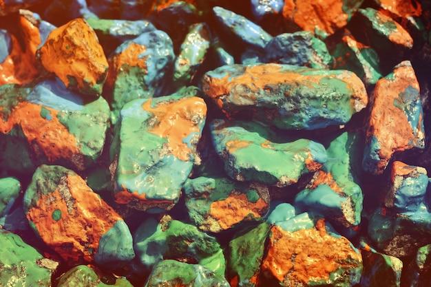 Pietra del primo piano intrisa di vernice arancione, blu e verde