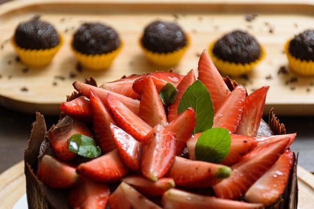 Primo piano di fragole con foglia di basilico e confettura di more, sulla torta al cioccolato, con intorno piatti di cioccolato. in sottofondo il brigadiere (dolce brasiliano).
