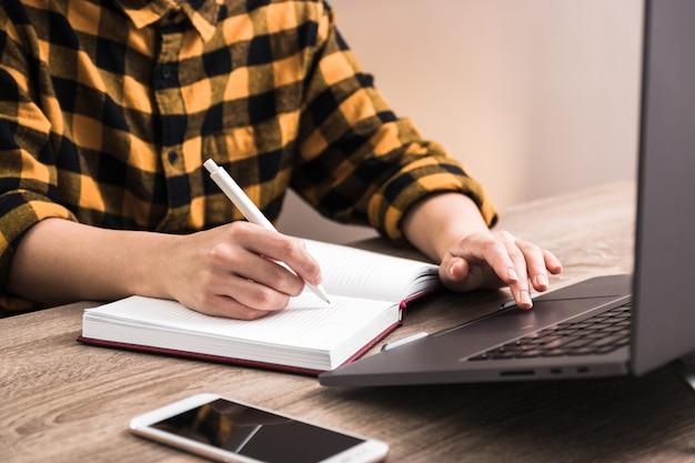 Lo studente del primo piano prende l'esame online via internet sul computer portatile e prende le note. apprendimento a distanza in caso di crisi pandemica