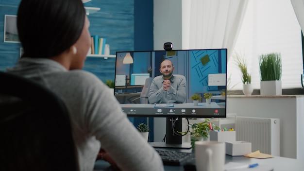 Primo piano di uno studente che parla con un imprenditore che discute idee di marketing con riunione in videochiamata