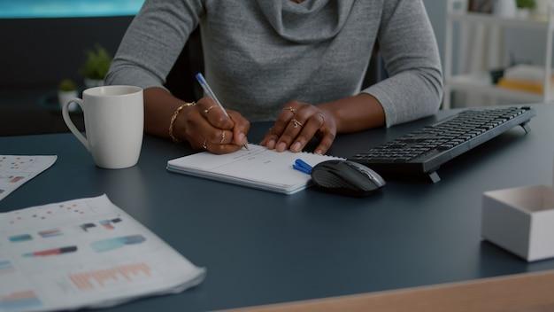 Primo piano dello studente con la pelle nera che scrive i compiti di comunicazione sul taccuino