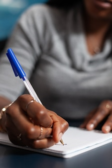 Primo piano dello studente con la pelle scura che scrive i compiti dell'università sul taccuino