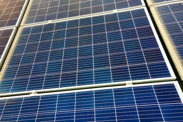 Primo piano della superficie dei pannelli solari fotovoltaici blu montati sul tetto dell'edificio per la produzione di elettricità ecologica pulita. produzione del concetto di energia rinnovabile.