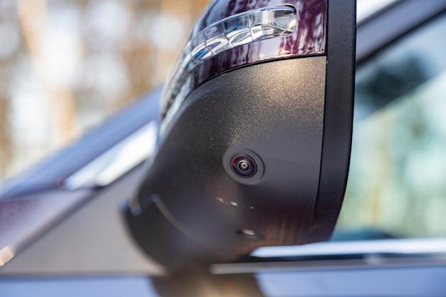 Primo piano di una telecamera con vista surround nello specchietto laterale di una moderna vista posteriore di un'auto. telecamera di parcheggio assistito