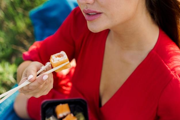Il set di sushi del primo piano tocca le labbra. la ragazza attraente tiene il sushi con le bacchette in mano. il corriere ha consegnato il set di sushi per una bella donna. scatola nera con sushi, wasabi, zenzero.