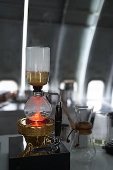 Primo piano sifone o caffettiera a sifone che produce caffè espresso caldo sul tavolo bar in caffetteria