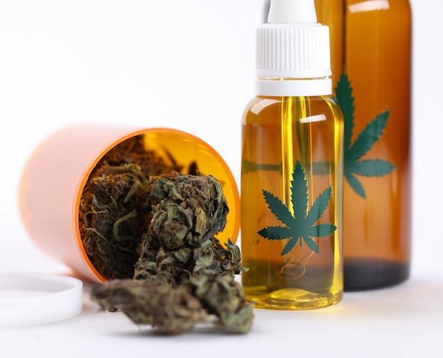Primo piano sull'olio di canapa della tavola e sull'erba secca della cannabis