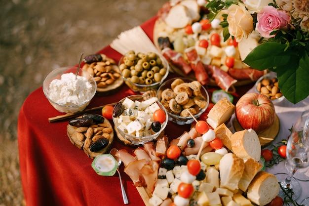 Primo piano di un tavolo con insalatiere con olive e mandorle di formaggio blu su una tovaglia rossa