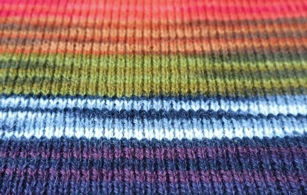 Primo piano la trama del tessuto di lana lavorato a maglia di alpaca a strisce colorate in motivi orizzontali