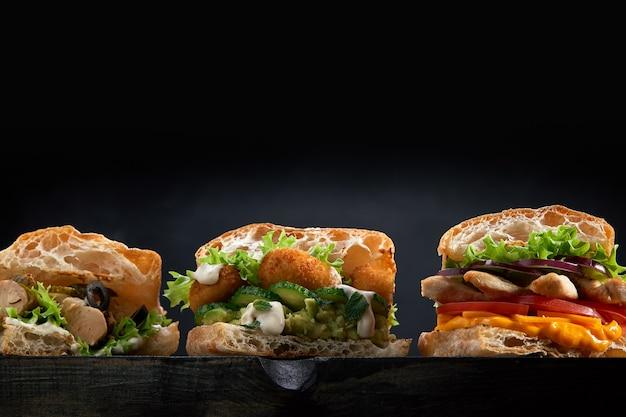 Primo piano di tre diversi panini appetitosi hamburger su fondo di legno nero