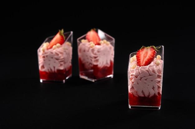 Primo piano di tre bicchieri riempiti con panna montata rosa e marmellata rossa decorata con frutti di bosco freschi e piccole palline bianche croccanti sulla parte superiore. dessert di fragole dolci isolati su sfondo nero.