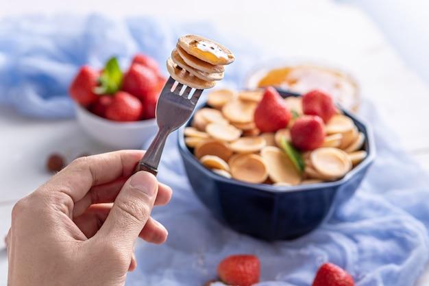 Primo piano minuscole frittelle di cereali sulla forcella, fragola, cibo alla moda