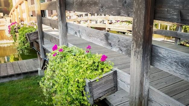 Immagine tonica di chiusura di bellissimi fiori che crescono in vasi sul vecchio ponte di legno sul canale dell'acqua nella città europea