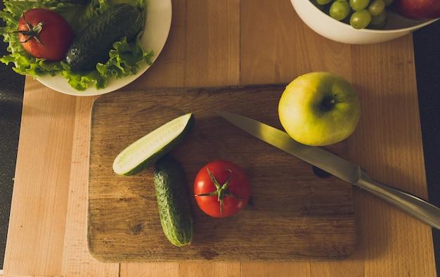 Foto dai toni del primo piano dall'alto di frutta e verdura sdraiata su una tavola di legno in cucina