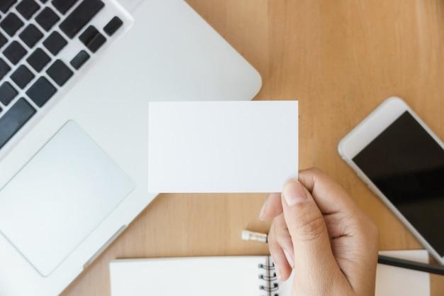 Closeup vista dall'alto foto donna mostrando vuoto biglietto da visita bianco e utilizzando moderno computer portatile e telefono cellulare sul tavolo in legno offuscata sfondo. mockup pronto per informazioni private. montatura orizzontale.