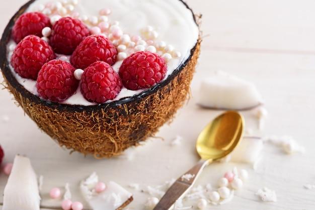Primo piano dessert alla moda con panna montata, lamponi e granelli di pasta nella ciotola di cocco con cucchiaio su sfondo bianco, ciotola frullato concept