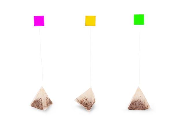 Bustina di tè del triangolo del primo piano con l'etichetta gialla isolata su fondo bianco