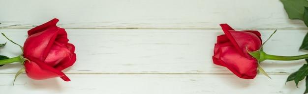 Un primo piano di due fiori di rose rosse di bellezza sulla plancia di legno con lo spazio della copia. utilizzando come flora natura e amore, il concetto di pagina di copertina di san valentino