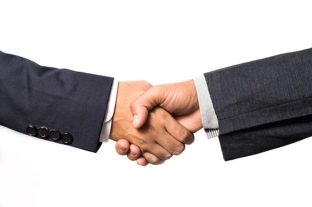 Un primo piano di una stretta di mano di due affari isolata su bianco