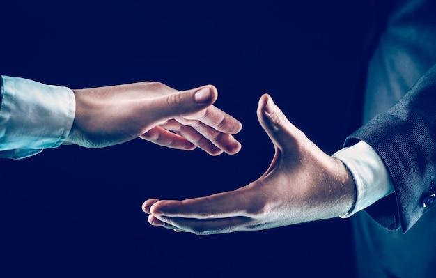 Primo piano di due uomini d'affari allunga la mano in avanti per una stretta di mano.foto su sfondo nero e ha spazio per il testo.