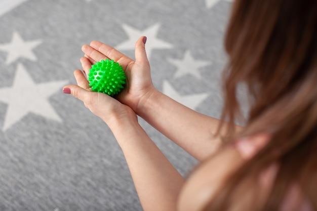 Le palme femminili del primo piano due tengono una sfera di massaggio appuntita verde