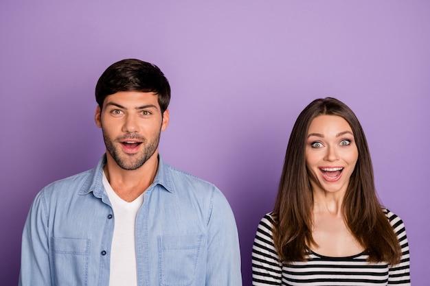 Primo piano due persone divertenti coppia emozioni positive buon umore bocca aperta ascoltare notizie incredibili indossare abiti casual elegante vestito isolato muro di colore viola pastello