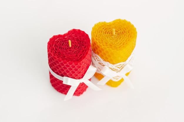 Primo piano di due candele di cera d'api naturali decorative di colore a forma di cuore rosso e giallo con nastri di pizzo e un aroma di miele per interni isolati su una parete bianca