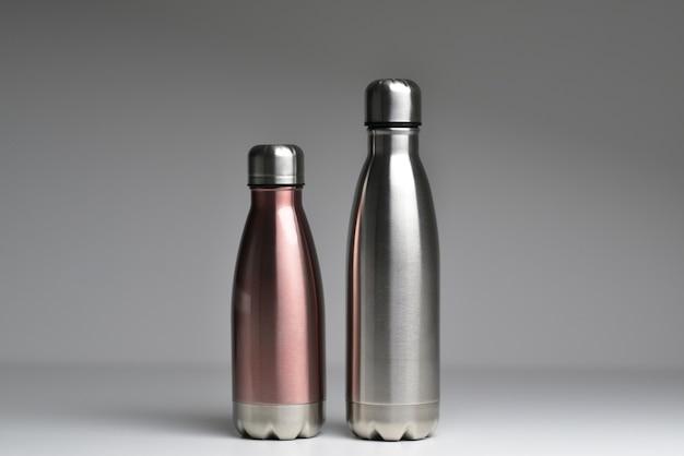 Primo piano di due bottiglie d'acqua termiche in acciaio riutilizzabili isolate su sfondo grigio con spazio di copia