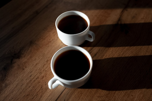 Primo piano di due tazze di caffè in ceramica bianca con ombre sul tavolo di legno.