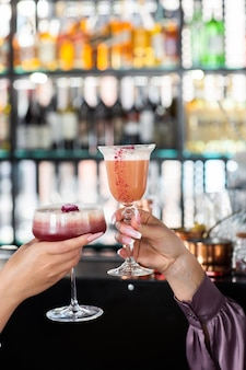 Primo piano di due donne che tengono cocktail freschi estivi. concetto di estate. saluti.