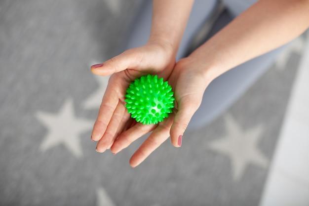 Le mani delle due donne del primo piano tengono una palla verde a spillo di massaggio