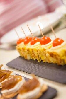 Primo piano di tipiche omelette spagnole tapas e formaggio con cipolla caramellata pinchos in un bar
