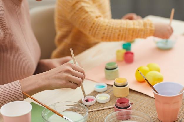 Primo piano di irriconoscibile madre e figlia che dipingono i colori pastello delle uova di pasqua che si siedono al tavolo nell'interno accogliente della cucina, lo spazio della copia