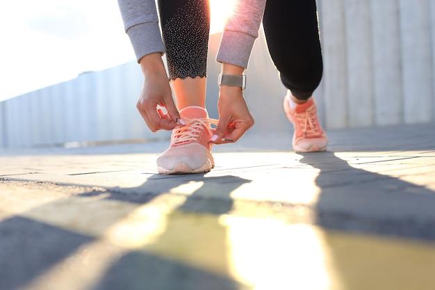 Primo piano di una donna sportiva irriconoscibile che lega scarpe sportive durante la corsa serale all'aperto.