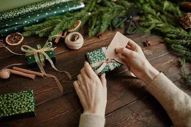 Primo piano di una giovane donna irriconoscibile che avvolge i regali di natale su uno spazio di copia di un tavolo in legno rustico