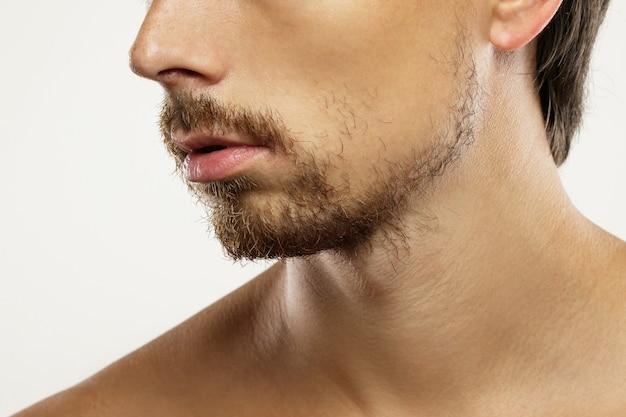 Primo piano del viso maschile non rasato con la barba incoltat