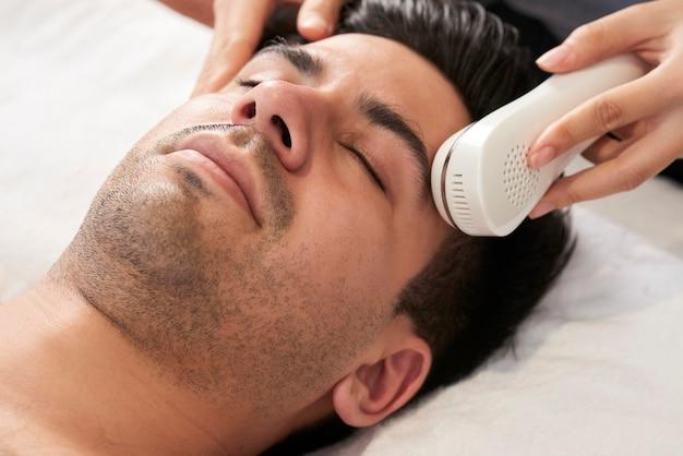 Immagine ravvicinata di un bel giovane che si sottopone a una procedura di bellezza nel salone della stazione termale