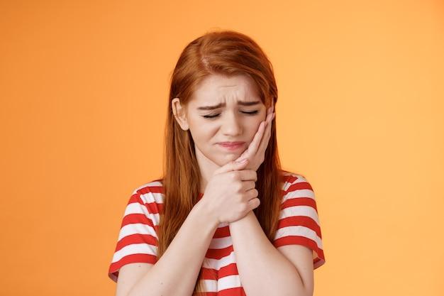 Primo piano sconvolto carina ragazza rossa a disagio soffre di mal di denti tenere la mano guancia accigliata chiudere gli occhi terribile per...