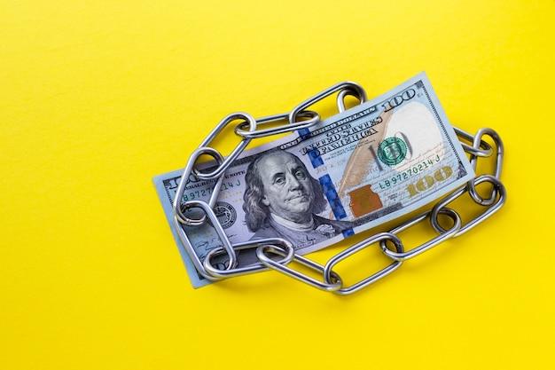 Primo piano di 100 centinaio di dollari usa sotto catena metallica su giallo