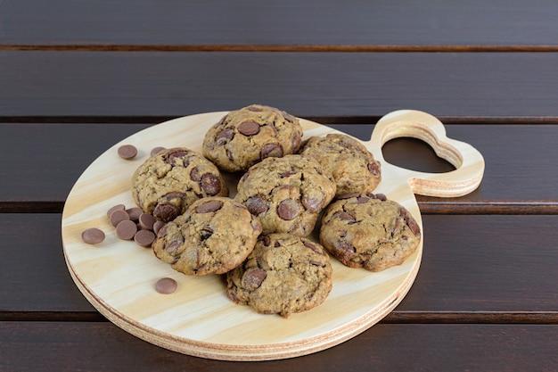 Primo piano di vari biscotti su una tavola di legno. accanto a gocce di cioccolatini.