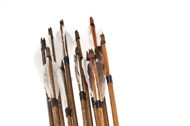 Vista ingrandita di antiche frecce in legno con piume grigie isolate