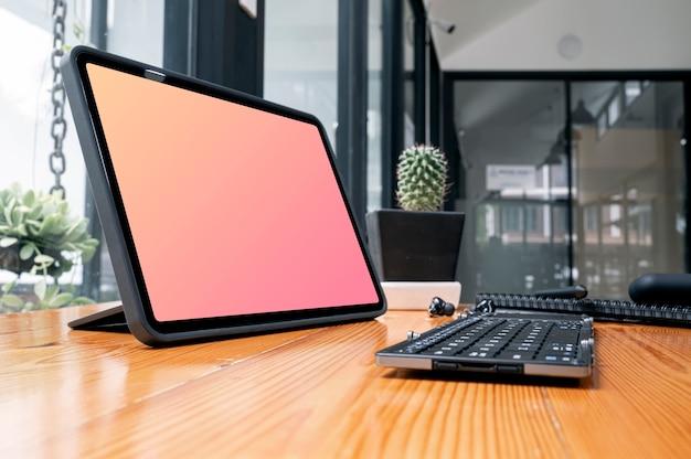 Vista del primo piano della compressa portatile dello schermo in bianco con la tastiera sulla tavola di legno.