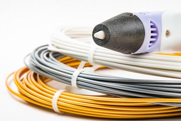 Vista ingrandita del mazzo di cavi laminati colorati e penna di stampa 3d per bambini isolata su bianco