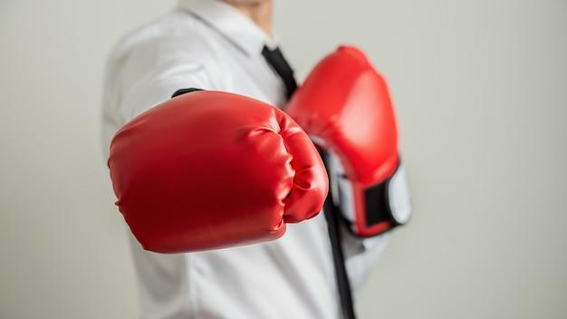 Vista del primo piano dell'uomo d'affari che indossa i guanti di inscatolamento rossi con una mano allungata direttamente alla macchina fotografica.