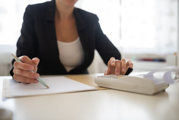 Primo piano di una donna d'affari seduta alla scrivania dell'ufficio che lavora su un rapporto, calcolando utilizzando la macchina additiva.