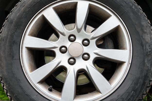 Una vista in primo piano di una ruota di un'auto con pneumatici invernali, disco freno argento e un cerchione a cinque dadi