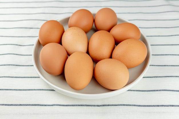 Vista ingrandita del piatto di ceramica pieno di molte uova di gallina marrone intero crudo su fondo tessile.