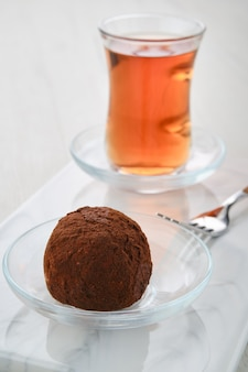 Vista ingrandita della torta di pasta biscotto al cioccolato e una tazza di tè su un tavolo