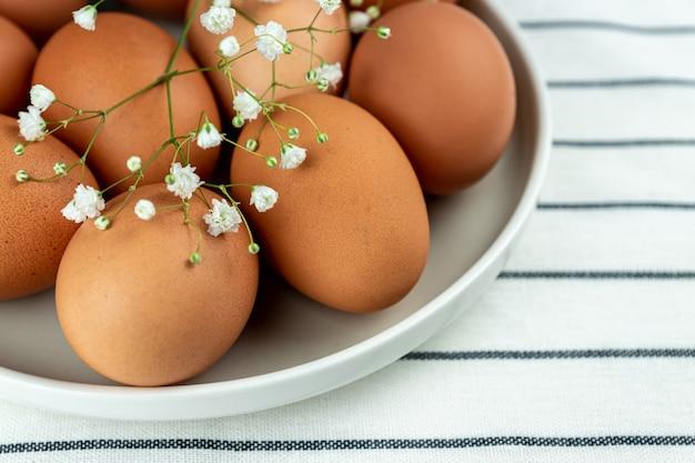 Vista del primo piano del piatto di argilla pieno di molte uova di gallina marrone intero crudo per cucinare cibo fresco fatto in casa.